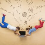 Cute boy and girl learning playfully in frot of a big blackboard. Studio shot on beige background.